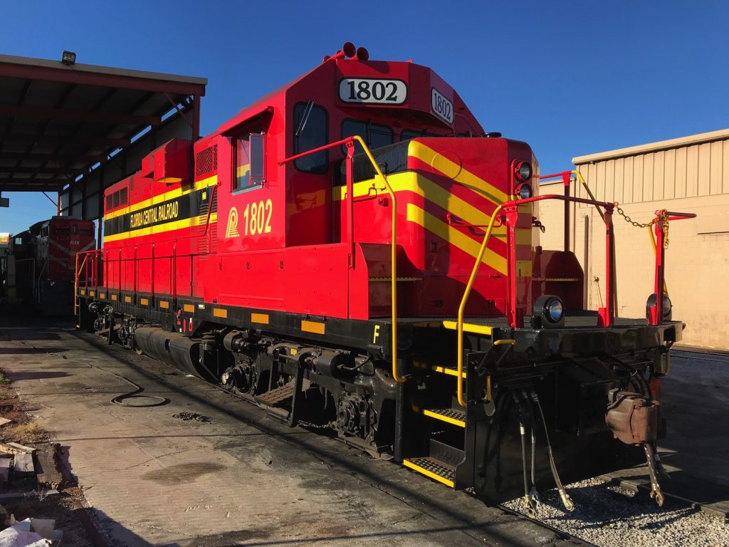 Red and yellow Florida Central locomotive #1802 proud in the late afternoon light