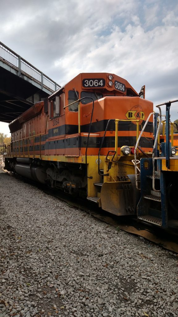 Orange B&P SD45 #3064, boots on the ground perspective, parked under a bridge