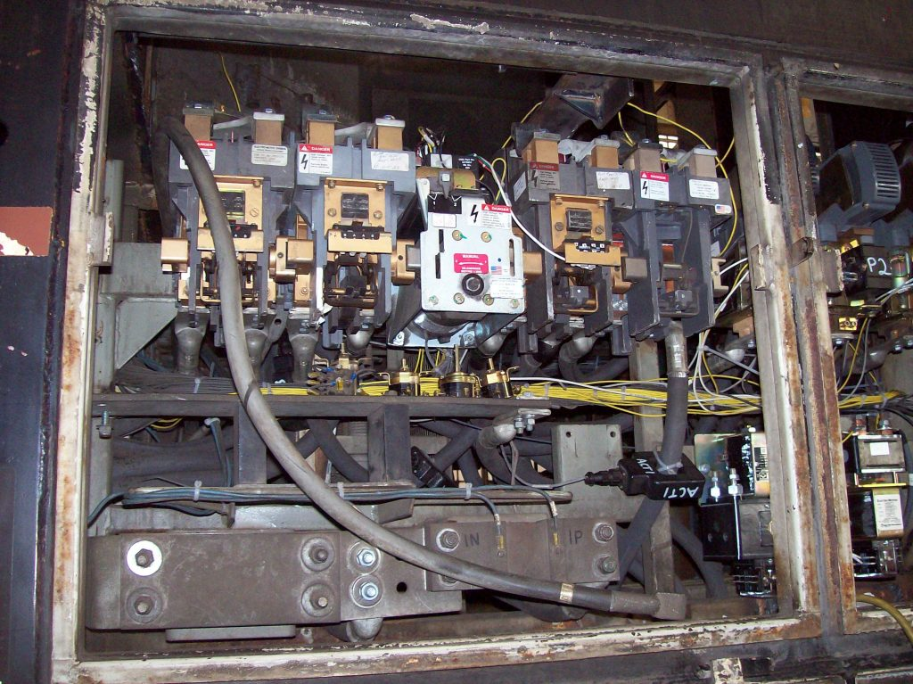 High voltage handling area of an MP15 locomotive, showing high voltage contactors, huge cables running through TMV 1800A current sensors to measure Armature current. Current Transducers.